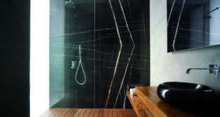Shower-with-a-large-black-marble-wall-and-wood-floor
